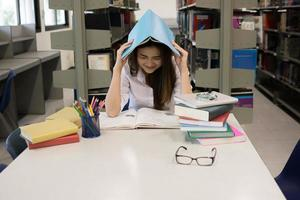 Portrait of student covering her head with a book while reading photo