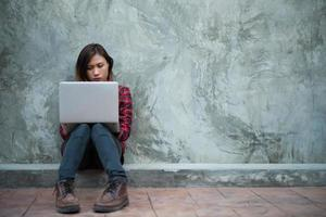 Feliz joven inconformista usando su computadora portátil mientras está sentado en el suelo foto