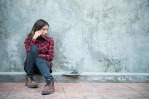 Young hipster woman in cool outfit sitting on the ground and talking on the phone photo