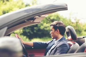 Handsome young man in sports car wearing a suit