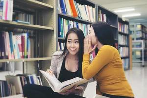 Group of happy students with books talking and preparing for exam in library photo