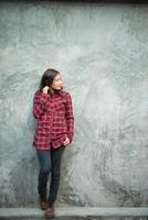 Beautiful young hipster standing in trendy clothes on grunge background photo
