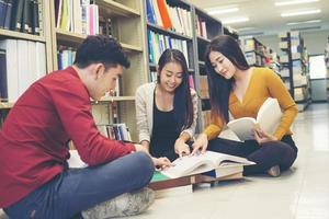 Group of happy students with books preparing for exam in library photo