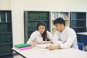 Pareja joven estudiante asiático en la biblioteca leyendo un libro juntos foto