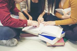 Grupo de estudiantes felices con libros preparándose para el examen en la biblioteca foto