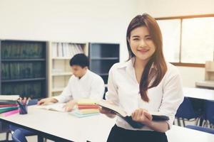 jóvenes estudiantes asiáticos en la biblioteca leyendo un libro foto