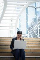 Business woman stressed while using laptop on the steps photo