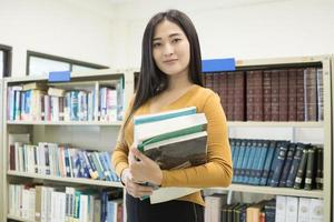 Joven estudiante bastante asiático sonriendo a la cámara foto