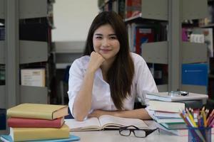 Joven estudiante bastante asiático sonriendo mientras lee en la biblioteca foto