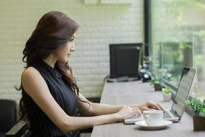 Young business woman working on laptop at office photo
