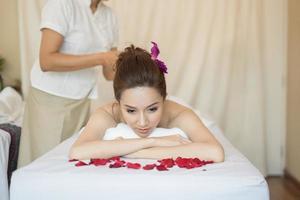 Mujer hermosa joven con masaje saludable en un salón de spa foto
