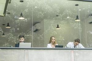 Felices colegas trabajando juntos en portátiles en la oficina foto