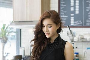 Young beautiful owner of cafe shop making coffee photo