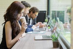 La empresaria tomando café mirando su computadora portátil mientras sus compañeros de trabajo interactúan en el fondo foto