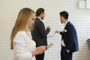 La empresaria mediante tableta digital mientras sus compañeros de trabajo interactúan en el fondo foto