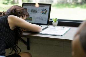 Mujer de negocios se duerme en el escritorio frente a su computadora portátil foto