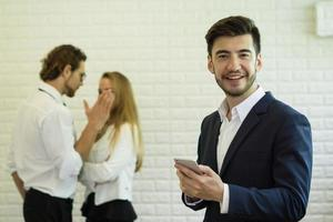 Businessman using smartphone while co-workers interact in the background photo