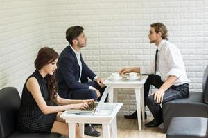 Group of young business co-workers in discussion at office photo