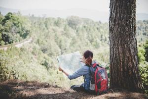 Young woman hiker reading a map while hiking photo
