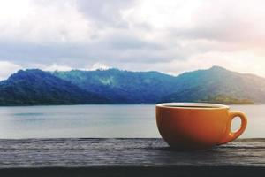 Coffee cup with hot drink on wood table with view mountain photo