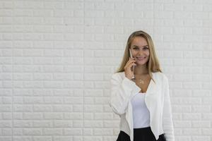 Señora de negocios joven que usa el teléfono inteligente mientras trabaja en la oficina