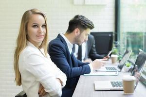 La empresaria usando la computadora portátil para trabajar mientras sus compañeros de trabajo interactúan en el fondo foto