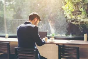 Young businessman wearing a suit and using laptop in a cafe photo