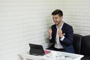 Exitoso joven empresario trabajando con un portátil en la oficina foto
