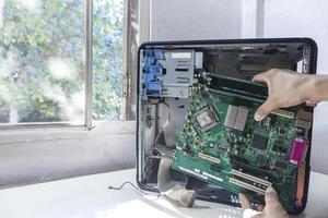 Young repairman technician fixing or upgrade mainboard on a case computer
