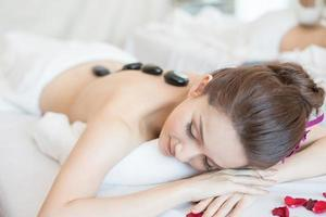 Hermosa joven recibiendo masaje con piedras calientes en el salón spa foto
