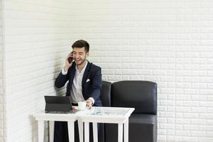 Joven empresario tomando un café trabajando en un portátil foto