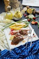 Bistec a la parrilla y papas fritas, con utensilios en un plato blanco con verduras en la mesa de madera oscura. foto