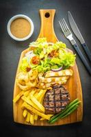 Grilled beef steak with french fries, sauce and fresh vegetables