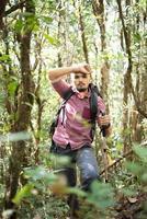 Caminante joven activo aunque el bosque a la montaña foto