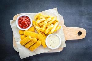 Fish finger and french fries with ketchup and mayonnaise sauce