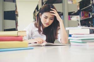 Retrato de estudiante tocando la cabeza mientras lee un libro en la biblioteca de la universidad foto