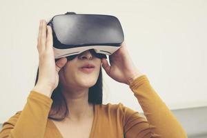Retrato de joven mujer asiática con gafas de realidad virtual foto