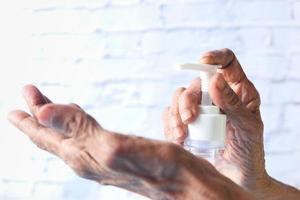 mano usando gel desinfectante foto