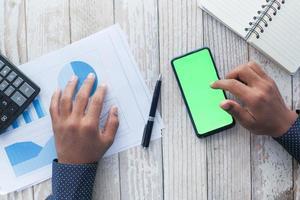 Vista superior de la mano del hombre con un teléfono inteligente en el escritorio de la oficina foto