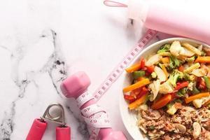 concepto de fitness con mancuernas, verduras frescas y cinta métrica foto