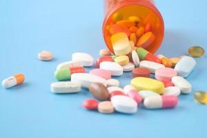 Cerca de muchas píldoras y cápsulas de colores sobre fondo azul.