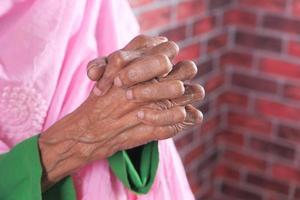 Cerca de las manos de la mujer mayor orando en Ramadán foto