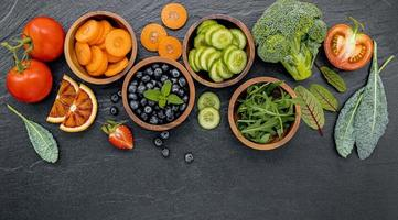 Bowls of fruit and vegetables on a dark background