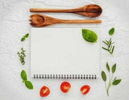 Spiral notebook with fresh herbs and tomatoes
