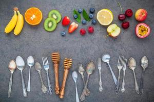Fresh fruit and utensils on a gray background