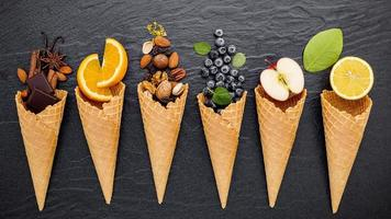 Fruit and nuts with ice cream cones on a dark background