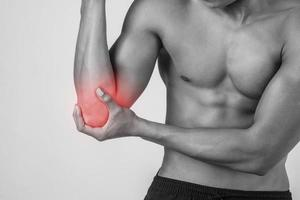 Portrait of a muscular man having elbow pain isolated on white background