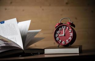 Books and alarm clock on wooden table