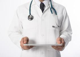 Young medical doctor holding a tablet pc isolated on gray background