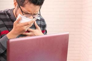 Man sneezing while working at a desk photo